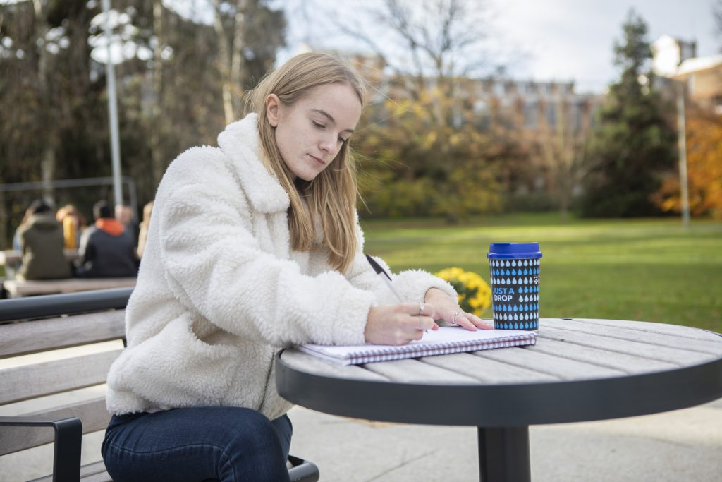 A photo of a student with a reusable coffee cup
